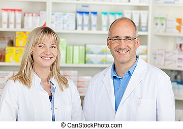confident team in pharmacy - male and female pharmacist...