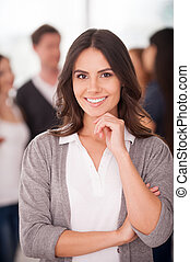 Confident team leader. Beautiful young woman holding hand on chin and smiling while group of people standing on background