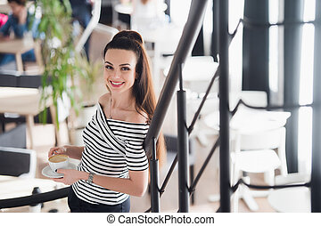 Confident team leader. Confident young woman holding a cup of hot coffee in her hands and looking at camera with smile while her colleagues working in the background.