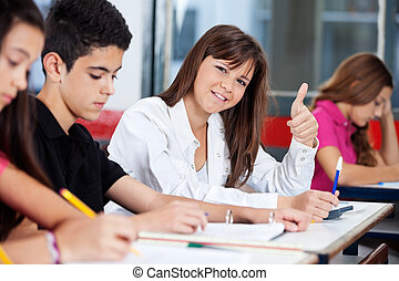 Confident Teenage Girl Gesturing Thumbs Up In Classroom