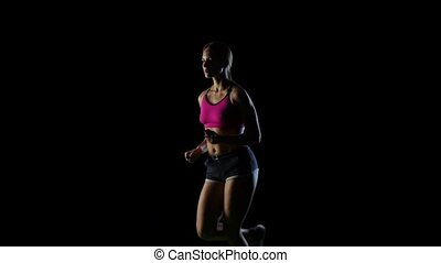 Confident the athlete runs in place on a black screen. Slow motion