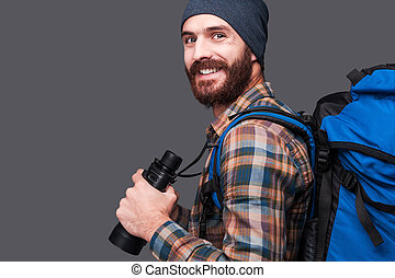 Confident tourist. Side view of handsome young bearded man with backpack holding binoculars and smiling while standing against grey background