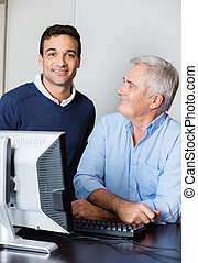 Confident Tutor With Senior Student In Computer Lab