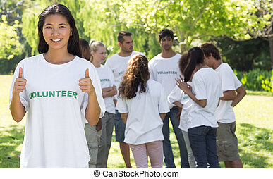 Confident volunteer gesturing thumbs up - Portrait of...