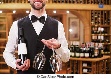 Confident waiter. Handsome young man in waistcoat and bow tie holding bottle and glasses while standing in liquor store
