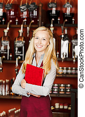 Confident Waitress Holding Book In Cafe