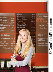 confident waitress standing in cafe