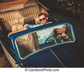 Confident wealthy young man behind classic convertible...