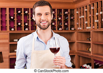 Confident winemaker. Confident young man in apron holding glass with red wine while standing in wine cellar