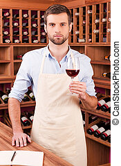Confident winery owner. Confident young man in apron holding glass with red wine while standing in wine cellar