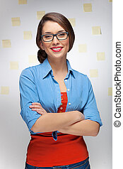 Confident woman. Beautiful young woman keeping her arms crossed while standing in front of the wall with adhesive notes on it