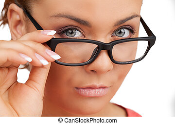 Confident woman. Close-up of confident young woman adjusting glasses and looking at camera