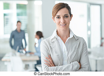 Confident woman entrepreneur posing in her office and smiling at camera, success and women empowerment concept