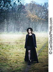 Confident woman in a black coat on the road