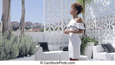Confident woman in dress posing on balcony