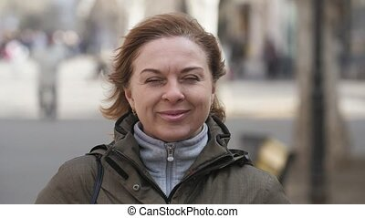Confident woman in jacket smiling and standing in a street...