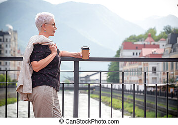 woman is resting on the bridge and looking at the magnificent mountains