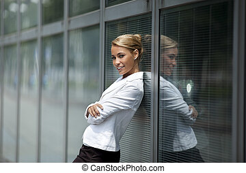 confident woman leaning on office building window - mid...