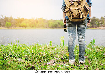 Confident woman posing on the shore of a wild lake, with mountains on the background, amazing tourist attractions