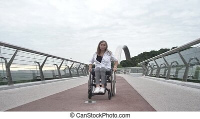Serious attractive disabled woman riding wheelchair on pedestrian bridge. Positive adult female with impaired mobility enjoying outdoor walk and active urban leisure despite disability