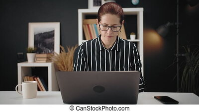 Confident woman sitting at table and working on laptop - ...