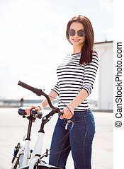 Confident woman standing near a bike