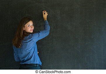 Confident woman teacher writing on blackboard background