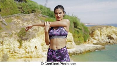 Confident woman training on shore - Beautiful serious woman...