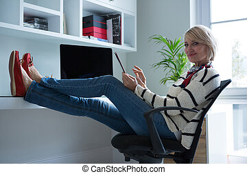 Confident woman using digital tablet at home