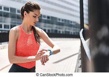 Confident woman using smartwatch for sport