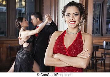 Confident Woman With Arms Crossed Standing While Dancers...