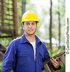 Confident Worker Carrying Ladder At Construction Site
