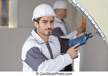 confident worker drilling a hole in the wall