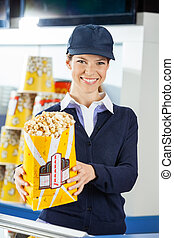 Confident Worker Holding Popcorn At Cinema Concession Stand