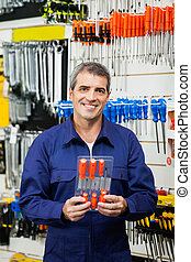 Confident Worker Holding Screwdriver Package - Portrait of ...