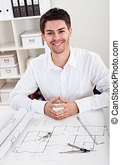 Confident young architect in his office