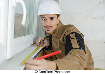 confident young builder measuring window