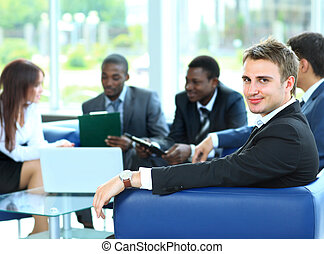 Confident young business man attending a meeting with his...