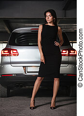 Confident young business woman standing near her car on parking