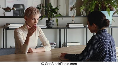 Confident young business woman vacancy candidate negotiating with employer, company recruiter at employment interview. Competent qualified female job applicant answering hr questions sitting at table.