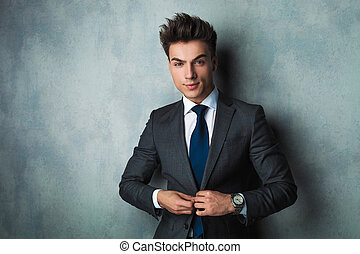 confident young businessman buttoning his suit