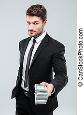 Confident young businessman giving money to you