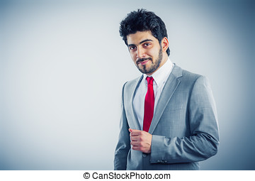 Confident young businessman is looking to the camera