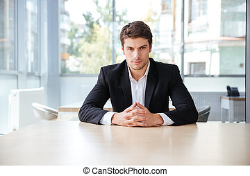 Confident young businessman sitting at the table in office