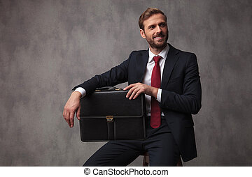 young businessman sitting with a suitcase and looks to side