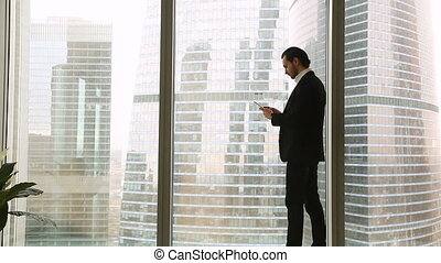 Confident young businessman standing near big window using...