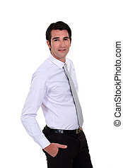 Confident young businessman stood with  hands in his pockets