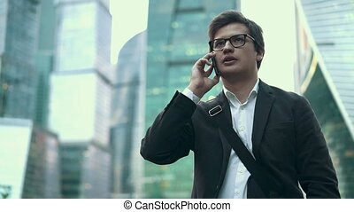 Confident young businessman talking on his phone in Moscow city, summer