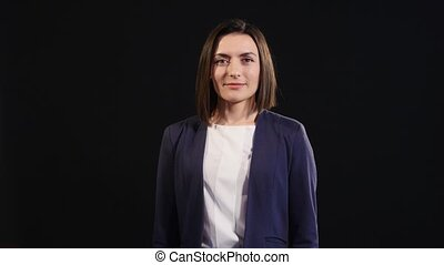 Confident young businesswoman giving the thumbs up against a black background