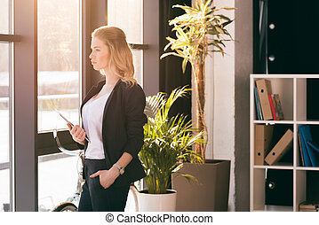 Confident young businesswoman holding digital tablet and looking at window in modern office